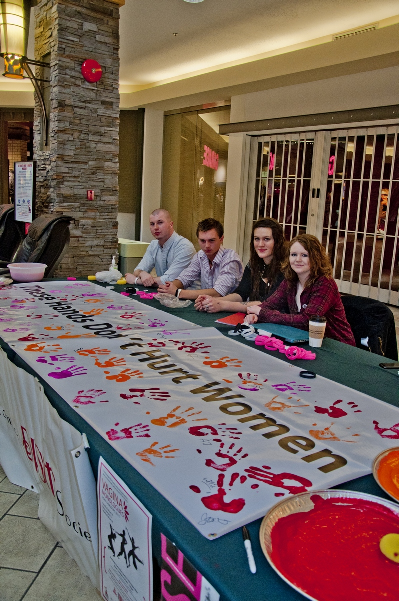 "Carver Stewart, Jon Ibsen, Gabrielle Putoto and Megan Graham sit with the ""These Hands Don't Hurt Women"" banner. They are four of the many young people involved with V-Day. - Photo by Courtney Dickson"