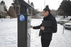 """Can I take a photo of you paying for parking?"" ""You mean the expensive parking?"" said Lacey Tallio as she dropped in her coins. Jessica Klymchuk/The Omega"