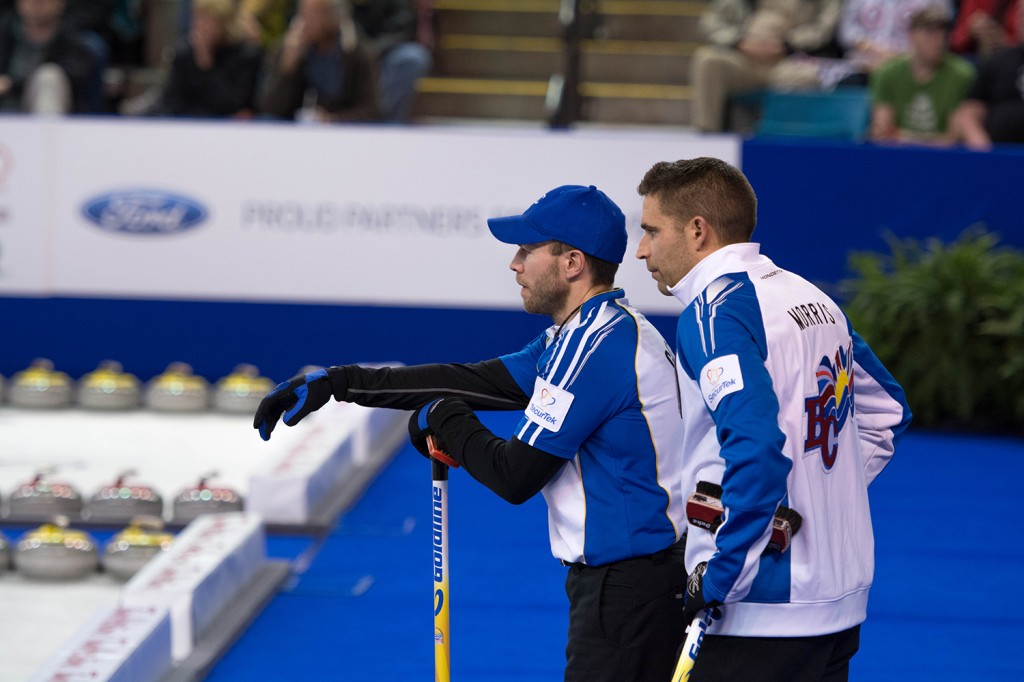 Morris and Cotter talk strategy while Team Koe out of Alberta does its thing in the second end of Friday night's playoff match. The B.C. rink won the match 9-5 after getting way ahead early thanks to a steal in the second end and a big three-point end in the fourth. Mike Davies/The Omega