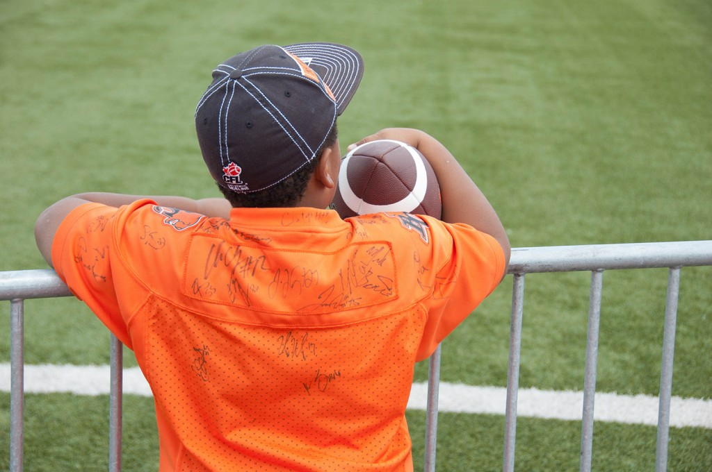 A young fan awaits the players' arrival with his ball ready for signing. -Mike Davies/The Omega