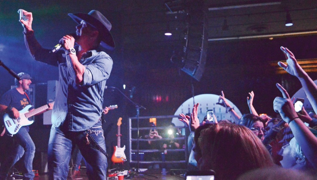 But first, let me take a selfie. Aaron Pritchett doesn't miss a beat while taking a selfie with an eager fan's phone during his Sept. 25 show at Cactus Jacks. (Marlys Klossner/The Omega)