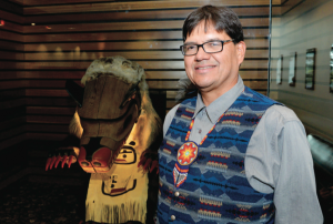 Paul Michel, in front of the indigenous artwork of the House of Learning. Michel believes a part of indigenization is making students aware of all the aboriginal artwork they see around campus. (Thompson Rivers University)