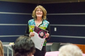 Eileen Leier holds Maxine Ruvinsky's notable women series poster in her hand while speaking on her time knowing Ruvinsky. (Ashley Wadhwani/The Omega)