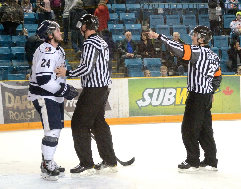Kamloops Blazers player Ryan Rehill yells at referee Kevin Bennett while linesman Riley Bilson stands between them.
