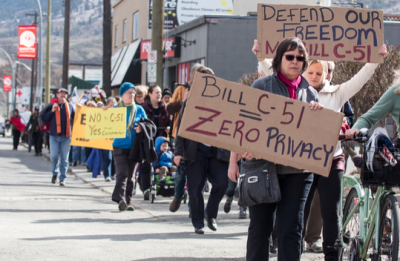 "Protesters marched from Cathy McLeod's office to Victoria St. on March 14 as part of the national ""Day of Action."" (Sean Brady/The Omega)"
