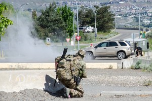 Smoke bombs are set off as a member of the RCMP Emergency Response Team looks on. (Jim Elliot/The Omega)