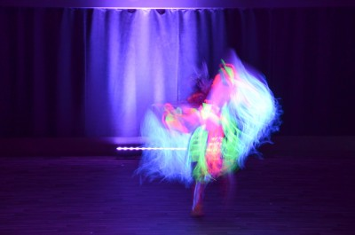 Under black light, an illuminated dancer moves across the stage. (Alison Hodgins/The Omega)