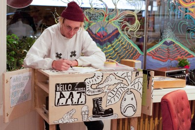Art host Ryland Fortie doodles while he mans the trailer. (Jared MacArthur/The Omega)