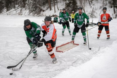 Snow flies as two players battle for the puck during the Logan Lake Pond Hockey Classic. (Tristan Davies/The Omega)