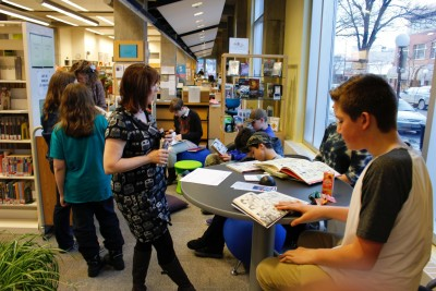 Susan McCowan (left of centre) looks on as club members examine some the graphic novels available at the library. (Jonathan Malloy/The Omega)