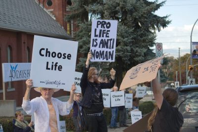 Pro-life and pro-choice protesters mix in front of Sacred Heart Cathedral. (Jennifer Will/The Omega)