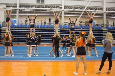 Cheerleaders in action, with coach Meaghan Blakely looking on. (Marcela Arévalo/The Omega)